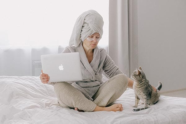Frau auf Bett mit Katze